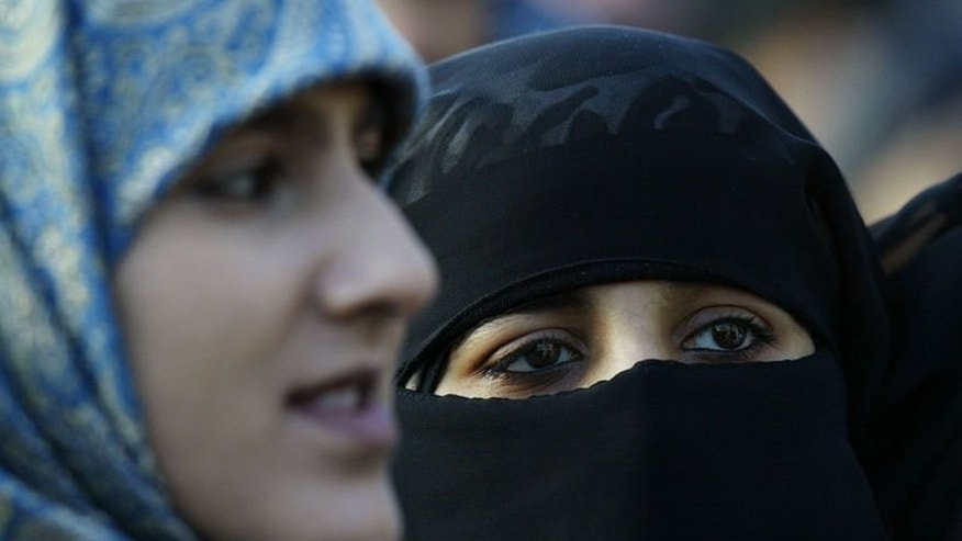 Veiled Muslim women stand at Marble Arch in London during a protest against French headscarf bans on January 17, 2004. One of Britain's biggest colleges on Friday dropped a ban on Muslim face veils after thousands of people signed a petition against the rule.