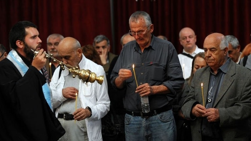 People attend a commemoration service marking the 35th anniversary of the death of Georgi Markov, a Bulgarian disident killed in London in 1978, on September 12, 2013 in a church in Sofia.