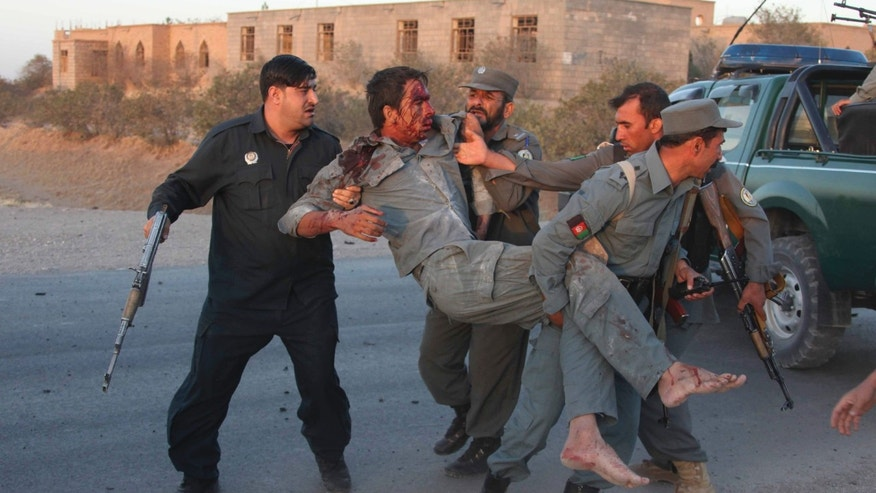 Sept. 13, 2013 - Afghan security personnel assist an injured police officer after a suicide car bombing and a gunfight near the U.S. consulate in Herat Province, west of Kabul, Afghanistan. Taliban militants attacked the U.S. consulate using a car bomb and guns to battle security forces.