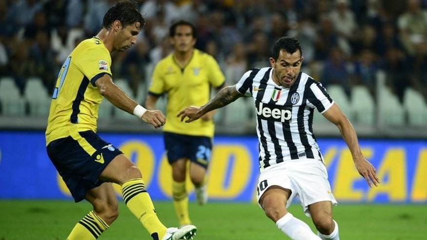 Juventus' Carlos Alberto Tevez (R) tries to get past Lazio's Lorik Cana during their Italian Serie A championship match on August 31, 2013 in Juventus stadium in Turin.