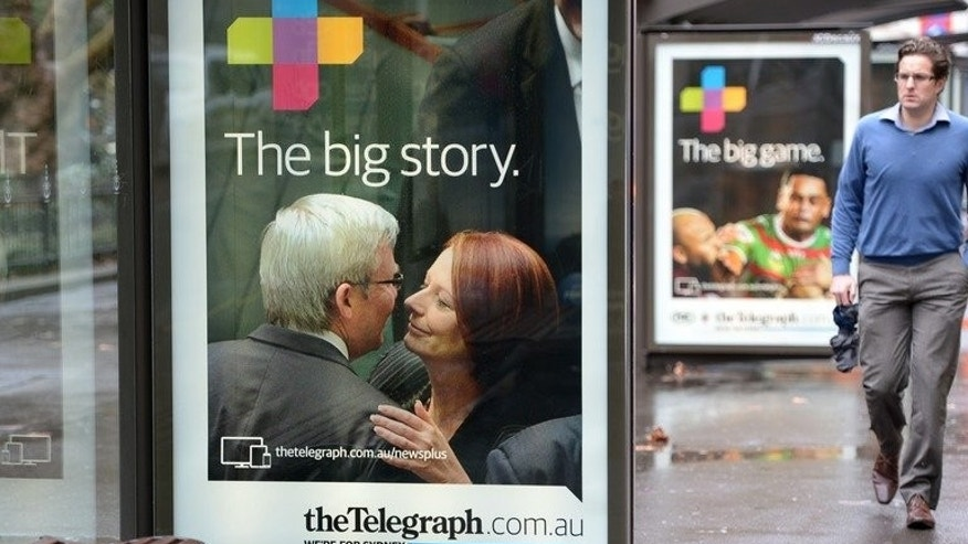 An advertising board showing outgoing Prime Minister Kevin Rudd (L) with deposed prime minister Julia Gillard is pictured at a bus shelter in Sydney on August 8, 2013.