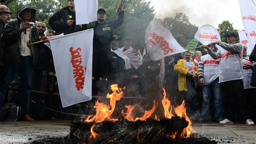 Members of Solidarity and other Polish trade unions burn a tyre as they demonstrate against the government's policies on September 11, 2013 in Warsaw.