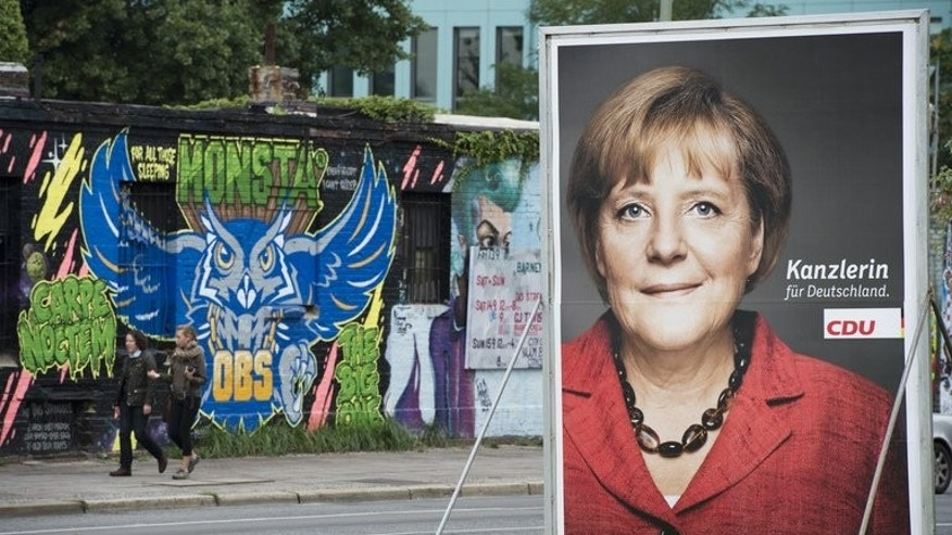 An election poster features German Chancellor Angela Merkel in Berlin on September 12, 2013. Merkel's election rival took more fire Friday for a magazine cover showing him making the vulgar middle-finger gesture, with many questioning his fitness to lead the nation.