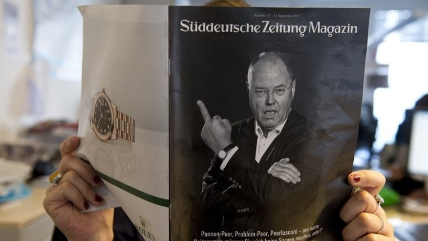 A woman holds a magazine supplement of Sueddeutsche Zeitung depicting Peer Steinbrueck giving the middle finger on September 13, 2013. German Chancellor Angela Merkel's election rival took more fire Friday for the cover.