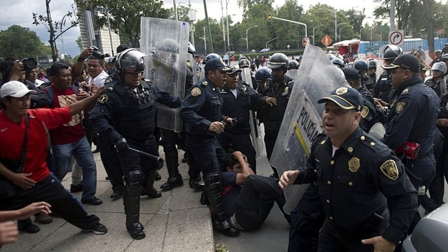 Riot policemen beat a teacher during a protest against the educational reform proposed by President Enrique Pena Nieto, along Reforma avenue in Mexico City on September 11, 2013.
