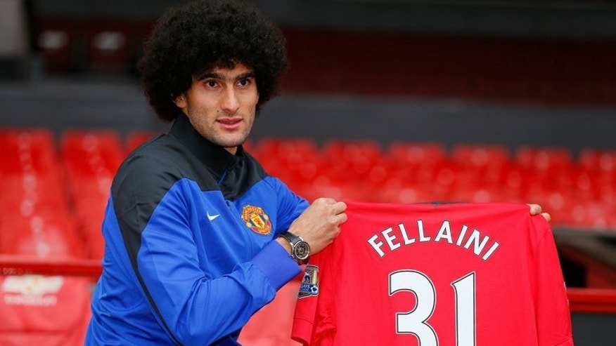 Manchester United's newly signed Belgian midfielder Marouane Fellaini poses with his shirt in Manchester, north-west England on September 13, 2013. Fellaini became Moyes first United signing for a fee of 27.5 million GBP (32.7 million Euros).