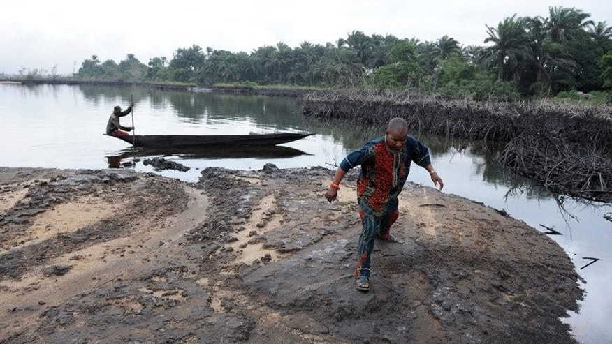 A man walks on slippery spilled crude oil on the shores of Bodo, a Nigerian village affected by oil spills in 2008, on June 24, 2010.