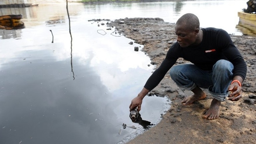 A man scoops spilled crude oil into a bottle from the waters of the Niger Delta swamps of Bodo, a village in the famous Nigerian oil-producing Ogoniland, which hosts the Shell Petroleum Development Company in Nigeria's Rivers State on June 24, 2010.