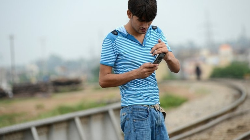 """A man checks his messages alongside a railway track in Rawalpindi. Pakistan has cracked down on """"immoral"""" love chat services offered by mobile phone companies, stifling hopes of illicit romance in the conservative Muslim country where dating is frowned upon."""