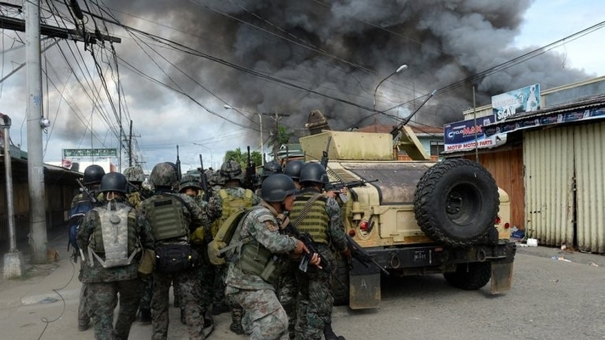 Philippines forces take cover during a fire fight with Muslim rebels in Zamboanga, Mindanao on September 12, 2013. At least 15 people have been killed, and nearly 200 Zamboanga residents are being used as human shields by the gunmen.