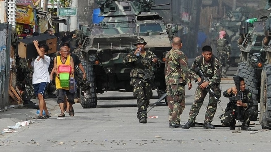 Zamboanga residents are evacuated during a fire fight between government forces and Muslim rebels on September 12, 2013. The rebels have been pinned down in a few largely Muslim communities in Zamboanga, setting fire to houses while firing at troops to keep them at bay.