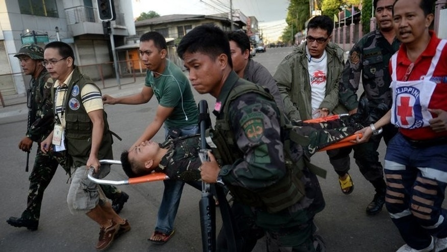 Awounded soldier is carried to an ambulance during a fire fight between Philippine troops and Muslim rebels in the Santa Catalina section of Zamboanga on September 13, 2013.
