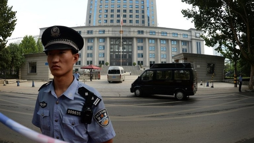 Police stand guard outside the Intermediate People's Court in Jinan, Shandong Province on August 25, 2013. Police on Friday detained an outspoken Chinese businessman who had called for the release of a prominent lawyer arrested as part of a crackdown on anti-corruption activists, a friend told AFP.