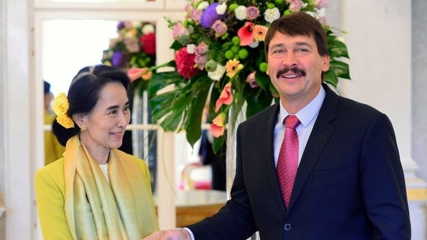 Myanmar's opposition leader Aung San Suu Kyi (L) is welcomed by the Hungarian President Janos Ader at Buda Castle in Budapest on September 13, 2013.