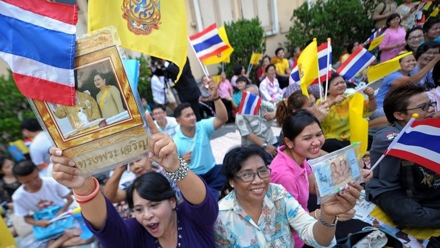 Well-wishers wave flags as they wait for Thai King Bhumibol Adulyadej to leave hospital in Bangkok on August 1, 2013. A Thai court on Friday acquitted a man held for nearly a year under royal defamation laws after his own brother accused him of insulting the king in their home.