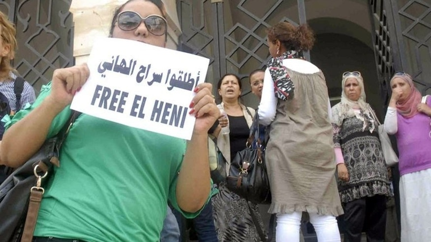 A Tunisian woman shows a poster during a protest outside Tunis courthouse against the detention of Zied el-Heni, a Tunisian journalist, on September 13, 2013.
