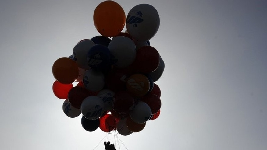 "A local television personality rides in a chair attached to 70 helium-filled balloons at a promotional event for the Disney/Pixar animated film ""UP,"" on May 13, 2009 at Walt Disney Studios in Burbank, California. An American adventurer's bid to float across the Atlantic to Europe in a rowboat suspended by a cluster of 370 helium balloons ended in failure after he was forced to land in Canada."