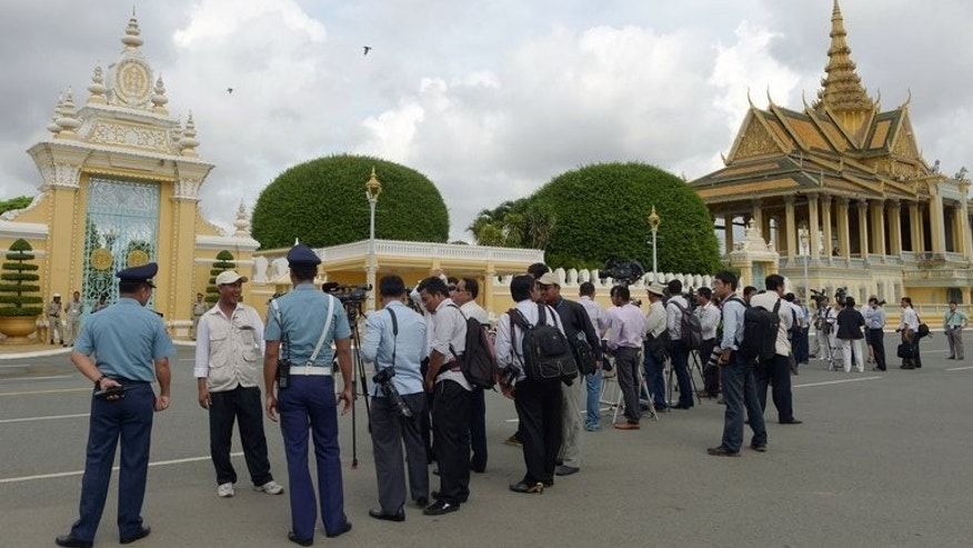 Journalists wait outside the Royal Palace in Phnom Penh during a meeting between Cambodian Prime Minister Hun Sen and opposition leader Sam Rainsy on September 14, 2013.