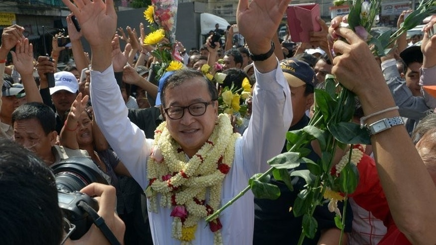 Sam Rainsy, leader of the opposition Cambodia National Rescue Party, greets supporters during a visit to a market in Phnom Penh on September 10, 2013.