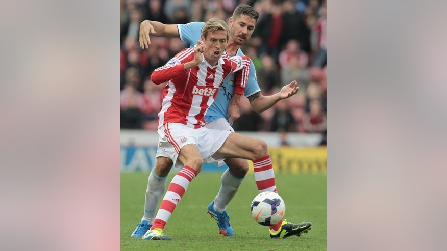 Stoke City's English striker Peter Crouch (front) vies with Manchester City's Spanish midfielder Javi Garcia (back) during the English Premier League football match between Stoke City and Manchester City at The Britannia stadium, Stoke-on-Trent, England, on September 14, 2013. The match ended 0-0.