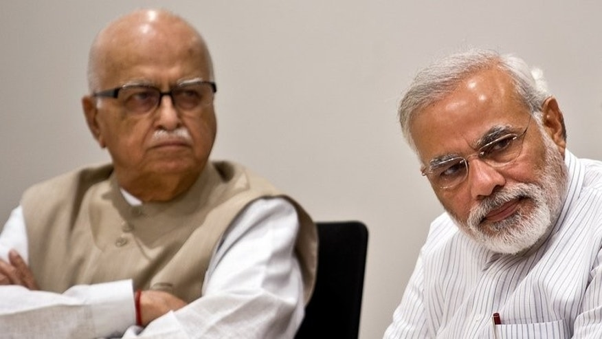 Narendra Modi (right) and senior party leader L.K. Advani (left) take part in a Bharatiya Janata Party (BJP) meeting in New Delhi on July 18, 2013. India's Hindu nationalist party scrambled Saturday to win support from the movement's most senior leader over a decision to anoint controversial politician Narendra Modi as candidate for premier in looming elections.