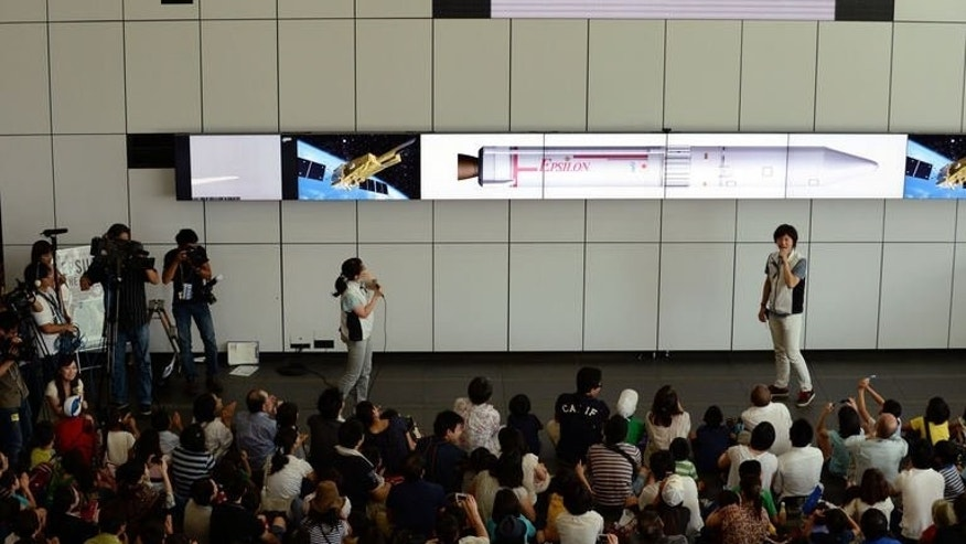 Guests watch a live transmission of the launch of Japan's new solid-fuel rocket on a screen at the Uchinoura Space Centre in Kagoshima, Japan on September 14, 2013.