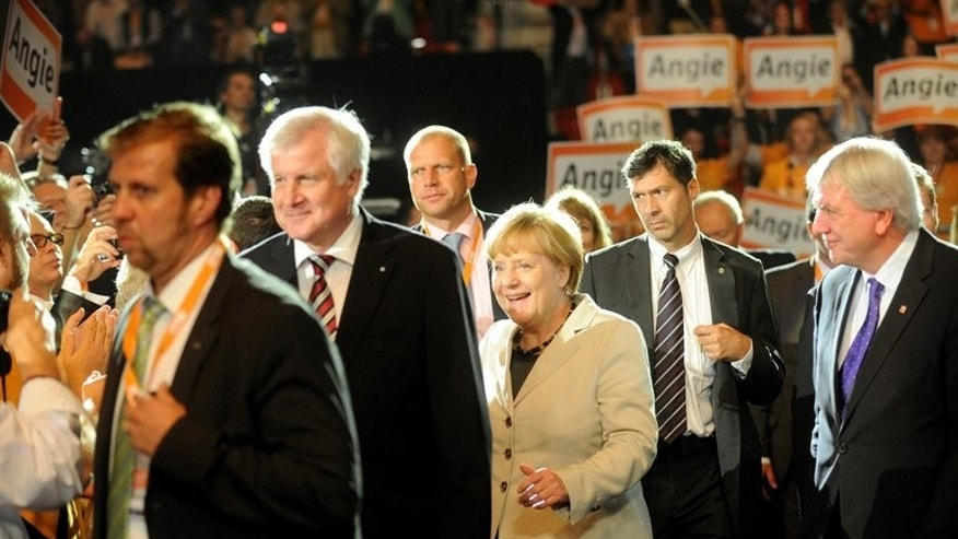 German Chancellor Angela Merkel (C) and State Premier of Bavaria Horst Seehofer (2ndL), arrive on September 8, 2013 for an electoral campaign meeting at ISS Dome in Duesseldorf, Germany.