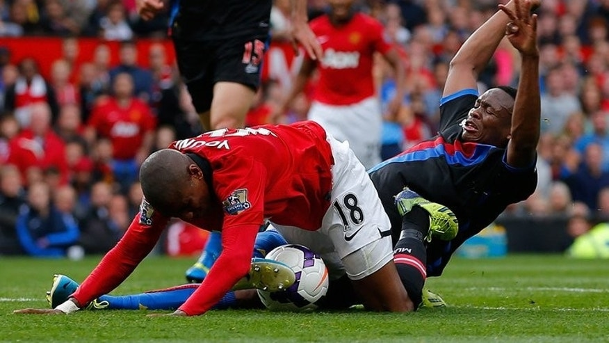 Manchester United midfielder Ashley Young (L) goes down under a challenge from Crystal Palace's Kagisho Dikgacoi during their Premier League match at Old Trafford in Manchester, northwest England, on September 14, 2013.