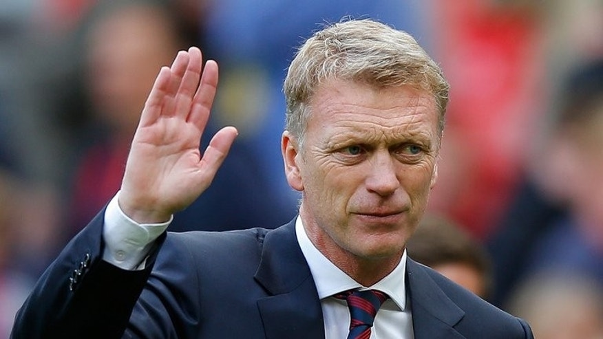 Manchester United manager David Moyes waves to the crowd as he leaves the pitch after his side's Premier League match against Crystal Palace at Old Trafford in Manchester on September 14, 2013.