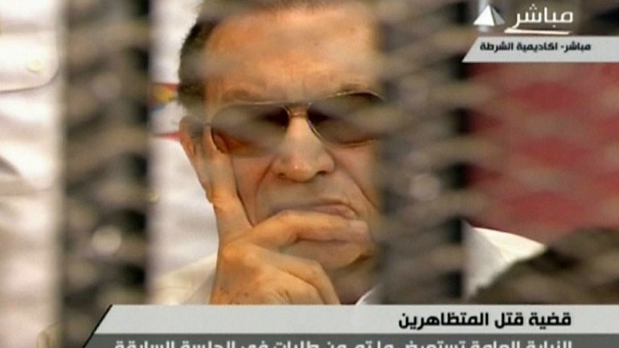 An image grab taken from Egyptian state TV shows ousted Egyptian president Hosni Mubarak behind bars during a hearing in his retrial in Cairo on July 6, 2013. An Egyptian court has resumed the trial of the toppled dictator, who is accused of complicity in the deaths of protesters during the 2011 uprising against his rule.