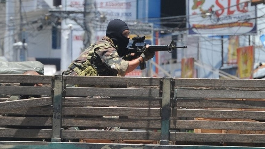 A Philippine soldier aims his weapon towards rebel positions as the stand-off between the two sides enters its sixth day in Zamboanga on September 14, 2013.