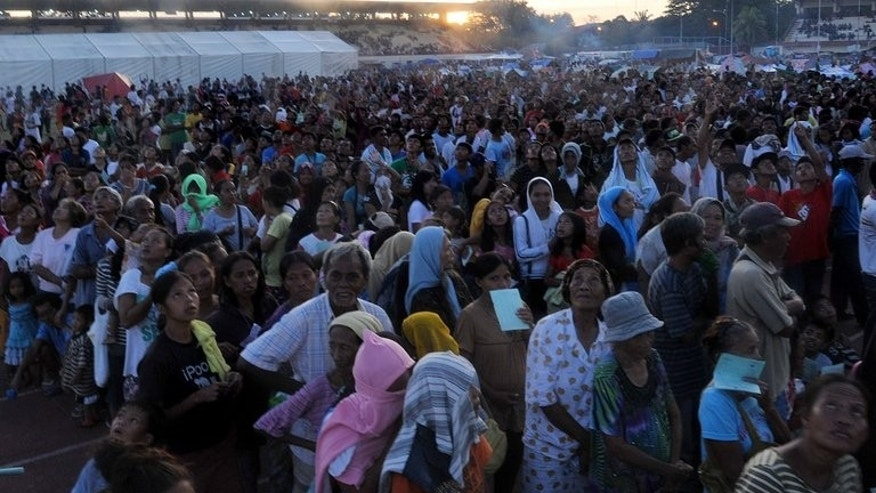 Evacuees affected by the stand-off between Philippine government forces and Muslim rebels queue up for food distribution inside a sports complex serving as temporary shelter in Zamboanga on September 14, 2013.
