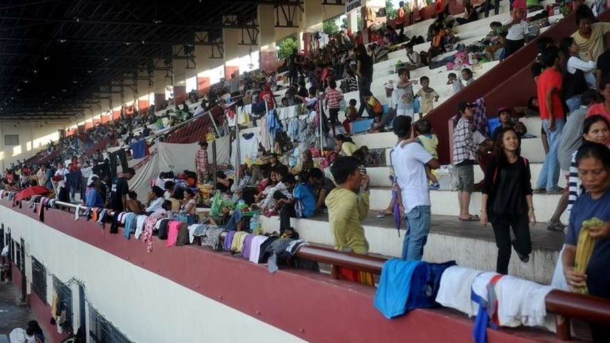 Evacuees affected by the stand-off between Philippine government forces and Muslim rebels crowd bleachers serving as their temporary shelter at a sports complex in Zamboanga on September 14, 2013.