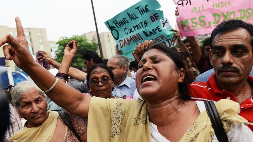 "An Indian woman shouts slogans calling for the death penalty for four men convicted of rape and murder outside the Saket courthouse in New Delhi on September 13, 2013. Indian rights groups voiced dismay Saturday over death sentences handed to four men for a fatal gang rape, saying it was unlikely to reverse the country's ""rape crisis"" despite a clamour for their execution."