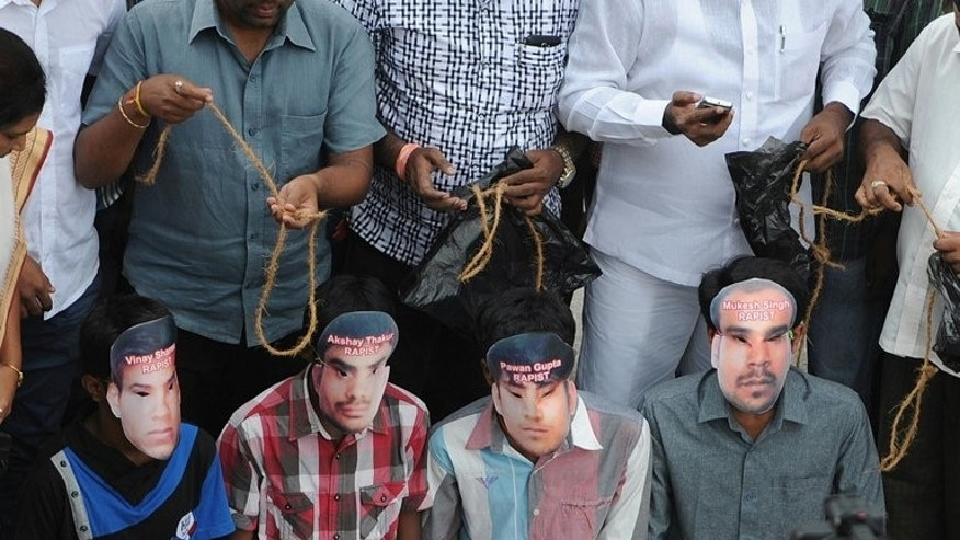 "Members of the Karnataka State Youth Congress, some of them wearing masks of four convicted rapists, enact a mock execution in Bangalore on September 13, 2013. Indian rights groups voiced dismay Saturday over death sentences handed to four men for a fatal gang rape, saying it was unlikely to reverse the country's ""rape crisis"" despite a clamour for their execution."
