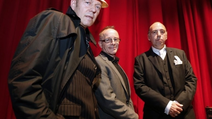 Members of the rock band The Clash, Paul Simonon (L), Topper Headon (C) and Mick Jones pose prior to giving a press conference, on September 12, 2013 in Paris.