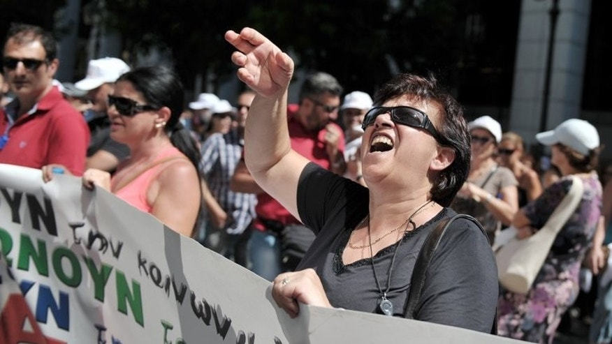 Demonstrators march outside the ministry of labour in Athens during a protest by civil servants on August 5, 2013 against cuts and job relocation