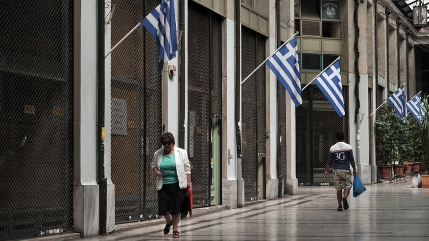 People walk through a shopping arcade in central Athens with most of businesses closed on September 12, 2013.