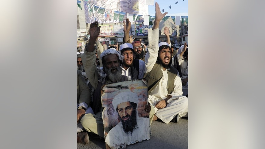 Supporters of hard line pro-Taliban party Jamiat Ulema-e-Islam carry a portrait of the slain Al-Qaeda leader Osama bin Laden as they shout slogans during a rally in Quetta on May 2, 2013. Afghan officials say Pakistan's release of 33 Taliban prisoners from jail, a policy initially trumpeted by Kabul as an opportunity to ignite peace talks, has resulted in no concrete progress.