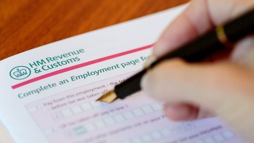 A woman fills a tax return form in London. A tax advisor to the British government was forced to resign after he was secretly filmed giving advice on how to avoid paying tax, officials have said.
