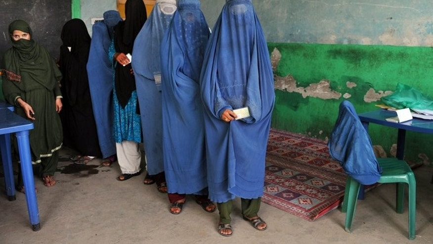 Afghan women wait in line to receive voter identification cards at a poll registration centre in Jalalabad on September 7, 2013.