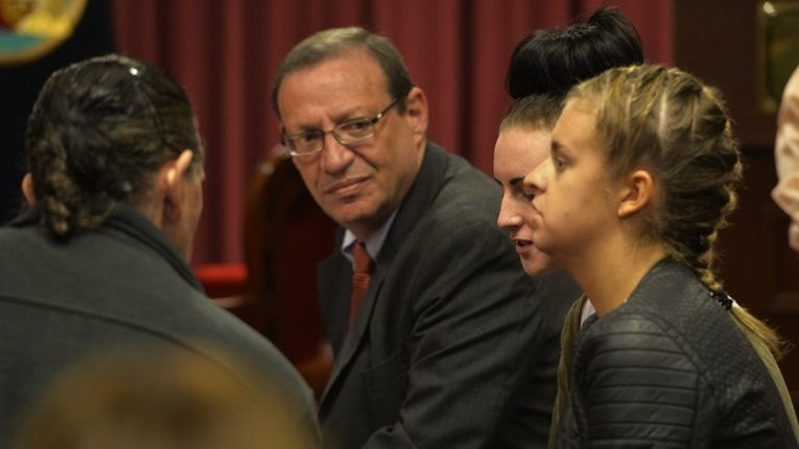 Irishwoman Michaella McCollum, 20, (C) and Briton Melissa Reid, 20, arrested at Lima's airport for carrying cocaine in their luggage, sit in a courtroom with their Peruvian lawyer Meyer Fishman (L), during a court hearing in Callao on August 21, 2013.
