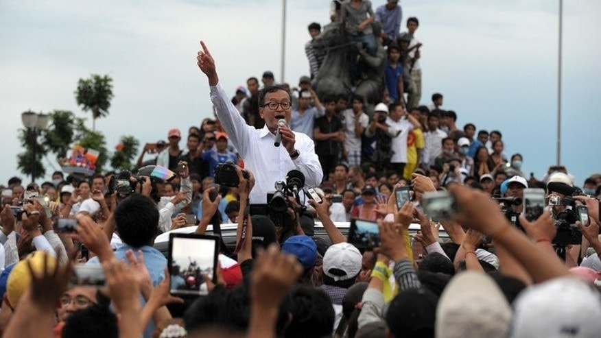 Leader of the opposition Cambodia National Rescue Party (CNRP) Sam Rainsy (C) speaks to protesters after clashes with police in Phnom Penh on September 15, 2013.
