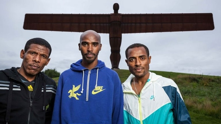 Ethiopia's Haile Gebrselassie, Britain's Mo Farah and Ethiopia's Kenenisa Bekele pose in front of the Angel of the North in Gateshead, northeast England on September 13, 2013. The three athletes take part in the Great North Run half-marathon event on September 15.