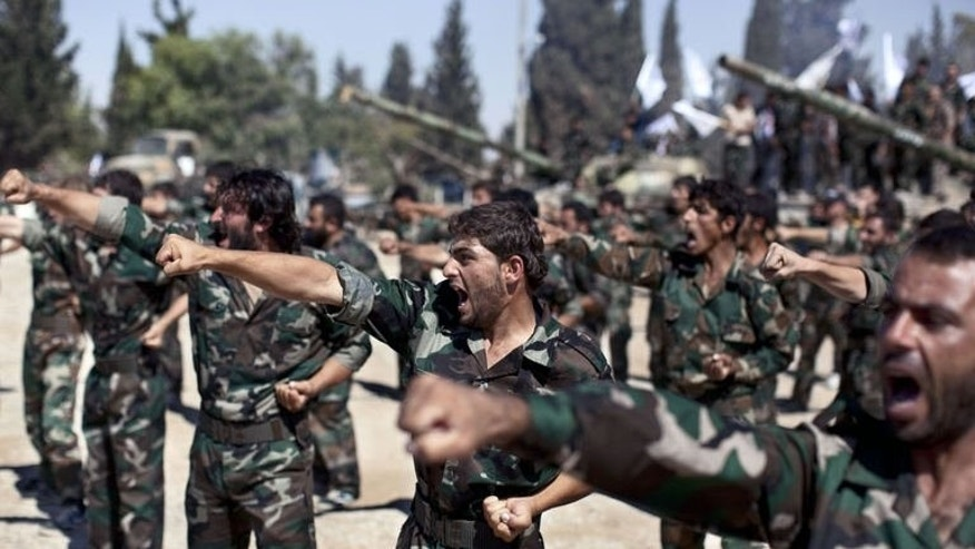Members of rebel brigades parade on September 13, 2013 at a former military academy north of Aleppo.