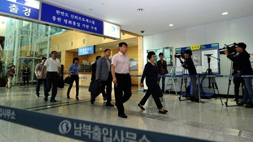Businessmen and women walk though a border checkpoint in Paju near the Demilitarized Zone (DMZ) dividing the two Koreas on September 16, 2013 as people head back to the North's Kaesong industry complex.