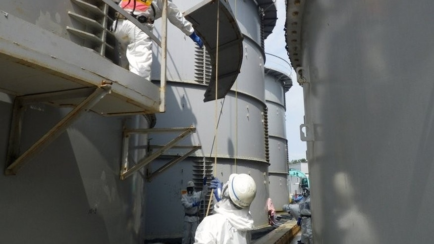 Image taken by TEPCO on September 13, 2013 shows workers preparing to take apart a contamination water tank where radioactive materials were leaked at the Fukushima Daiichi nuclear plant.