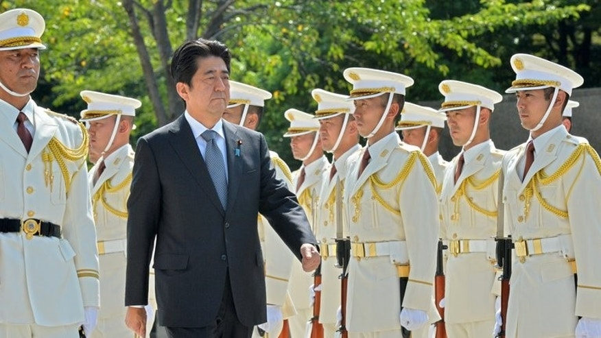 Japanese Prime Minister Shinzo Abe (2nd L) reviews honor guards at the defence ministry in Tokyo on September 12, 2013.