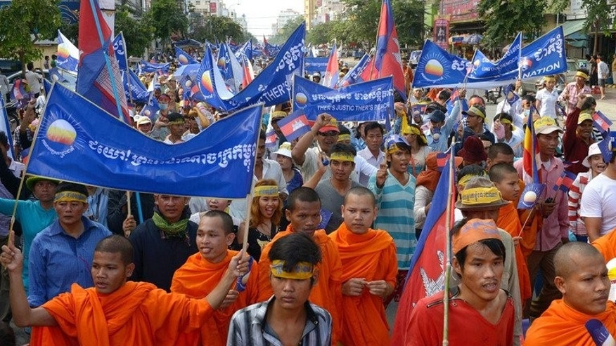 Buddhist monks join residents as they march along a street toward Democracy Park during a demonstration in Phnom Penh on September 15, 2013.