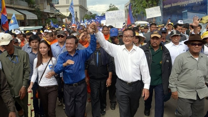 Sam Rainsy, leader of the opposition Cambodia National Rescue Party, (3rd R) and party deputy Kem Sokha raise their hands as they march along a street during a demonstration in Phnom Penh on September 15, 2013.